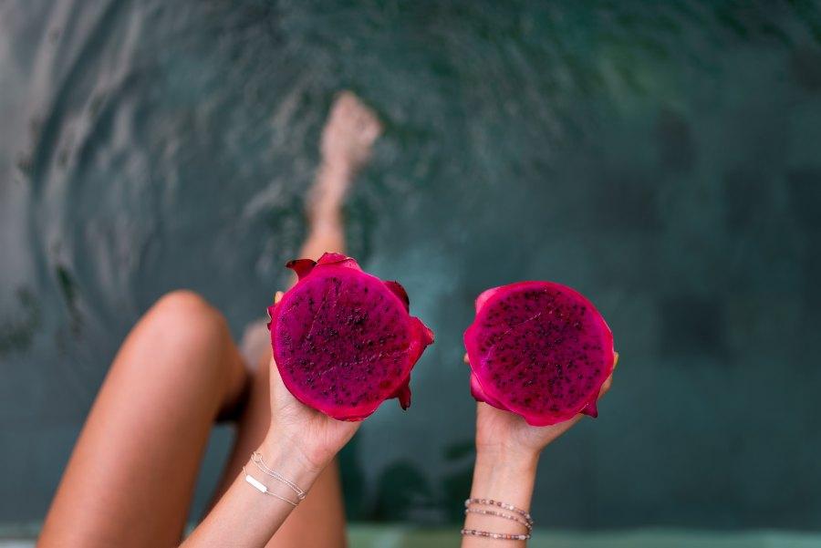 Anledningar att bli vegan - Vegansk mat. Foto på Rosa frukt i händerna på en tjej på en brygga